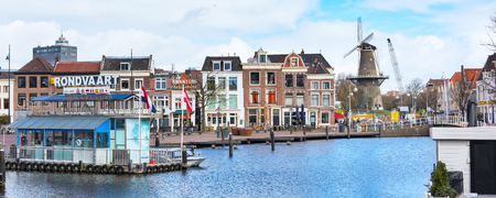 Leiden, Netherlands - April 7, 2016: Panorama with traditional dutch houses, harbour at canal and windmill in Holland