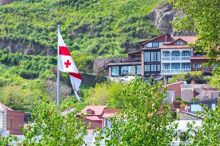 Tbilisi, Georgia - April 29, 2017: Georgian flag and houses in Old Town of Tbilisi, Republic of Georgia