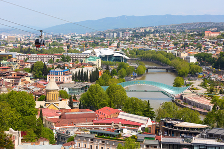Tbilisi, Georgia - April 29, 2017: Tbilisi red cable car cabins and aerial city skyline panoramic view