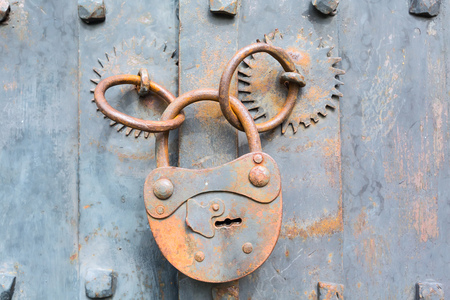 ensuring: Old rusty padlock on wooden door background with copyspace