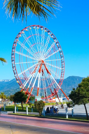 ferriswheel: Batumi, Georgia - April 30, 2017: Ferris wheel, city panoramic landscape with mountain peaks, summer Black sea resort Editorial