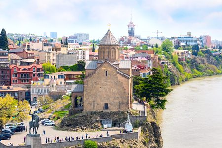 Tbilisi, Georgia - April 29, 2017: Aerial panoramic skyline with old traditional houses over Mtkvari or Kura river and Metekhi church Editorial