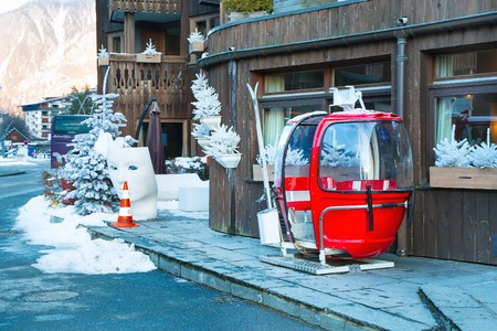 Chamonix, France - January 25, 2015: Old red cable car cabin in the street and white christmas trees