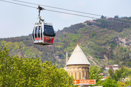 Tbilisi, Georgia - April 29, 2017: Tbilisi red cable car cabin and church tower Banco de Imagens - 85223347