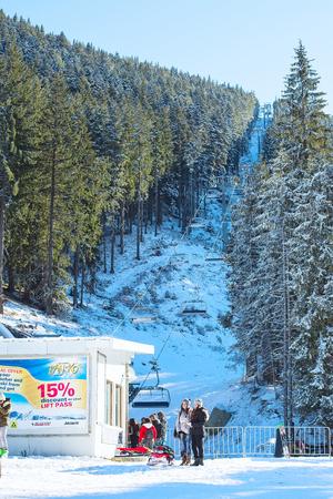 ski walking: Bansko, Bulgaria - December 12, 2015: Ski resort Bansko, Bulgaria, ski lift and mountain with pine trees, people Editorial