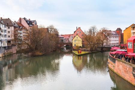 Neurenberg, Duitsland - 24 december 2016: Stadsstraat met traditionele huizen in Beieren in de kersttijd en uitzicht op de rivier