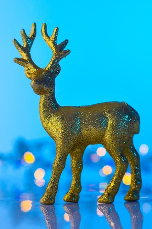 Christmas or New Year golden Reindeer, blue and turquoise bokeh background with lights 免版税图像