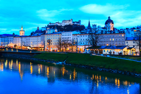 Evening twilight view of historic city of Salzburg with illuminated Cathedral and Hohensalzburg Festung across Salzach river in Austria Stockfoto