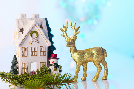 Christmas or New Year snow house, snowman and golden reindeer, blue and turquoise bokeh background with lights Stock Photo