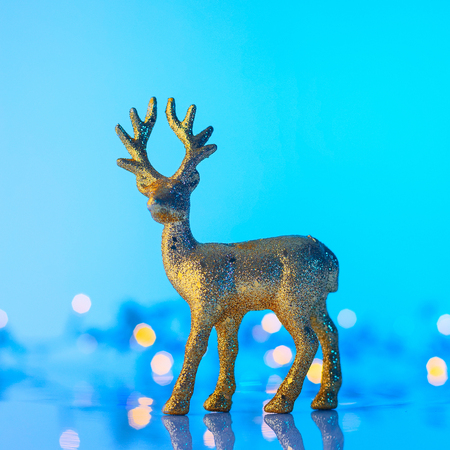 Christmas or New Year golden Reindeer, blue background with lights, copy space Stock Photo