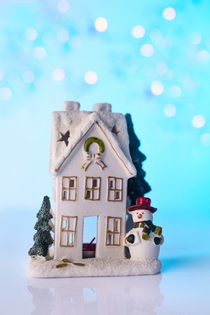 Christmas or New Year snow house, snowman, blue bokeh background with lights Stock Photo
