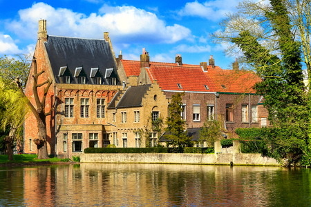 Iconic view in Bruges, Belgium at Minnewater lake, medieval houses against blue sky