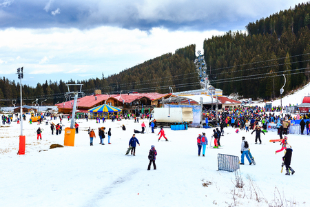 Bansko, Bulgaria - December 12, 2015: Bunderishka polyana, ski station, cable car lift and mountain with pine trees, people Editorial