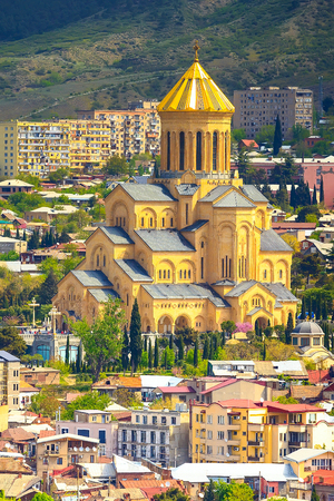 Tbilisi, Georgia aerial skyline with houses and Holy Trinity church or Tsminda Sameba Cathedral
