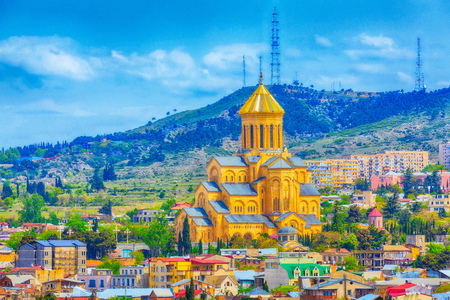 Tbilisi, Georgia aerial skyline with old traditional houses and Holy Trinity church or Tsminda Sameba Cathedral