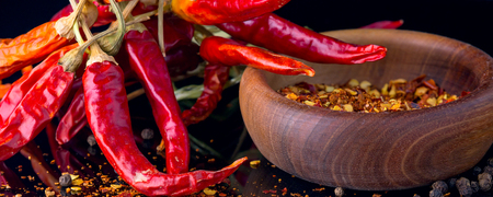Red chili peppers and chili flakes spices and herbs on black banner background with reflection and copy space