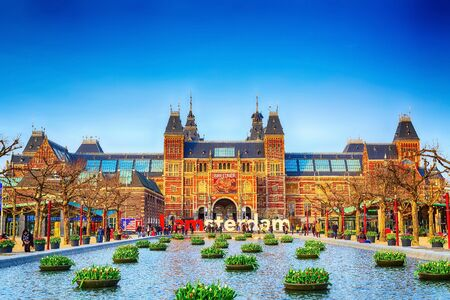 Amsterdam, Netherlands - March 31, 2016: Water and flowers, Rijksmuseum and people in front of writing, I amsterdam, Museumplein, Holland Editorial