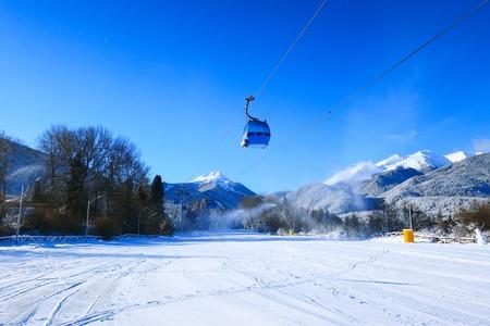 Bansko ski resort panorama with ski lift cabin, slope and snow mountains, Bulgaria Stock Photo