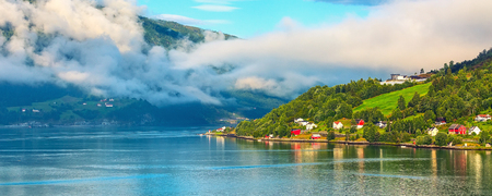 Norwegian village banner landscape with fjord, mountains, clouds and colorful houses in Olden, Norway