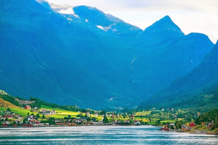 Norwegian village landscape with fjord, high mountains and colorful houses in Olden, Norway