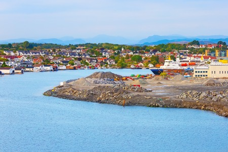 Harbor, ship and industrial infrastructure along the coast near Stavanger, Norway. Houses on background Stock Photo