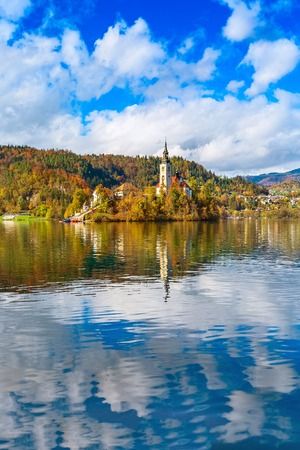 Panorama of Lake Bled with Church and Pletna boats, Slovenia and autumn colorful trees background