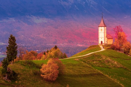 Autumn red sunset panorama with Saints Primus and Felician Church on top of hill in Jamnik, Slovenia countryside