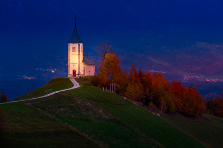 Autumn night panorama with Saints Primus and Felician Church on top of hill in Jamnik, Slovenia countryside