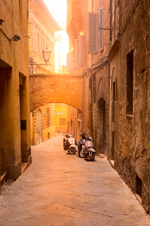 Italy landmark, Tuscany Siena medeival town, narrow street view and two scooters at sunset or sunrise