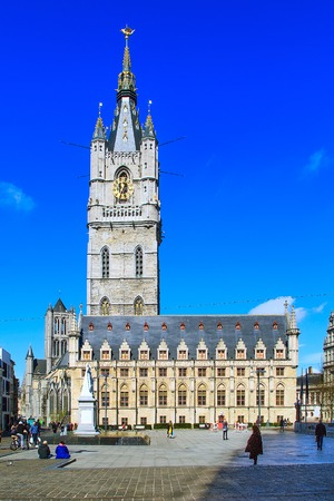 Ghent, Belgium - April 12, 2016: Grand Belfry with clock in Ghent on blue sky background