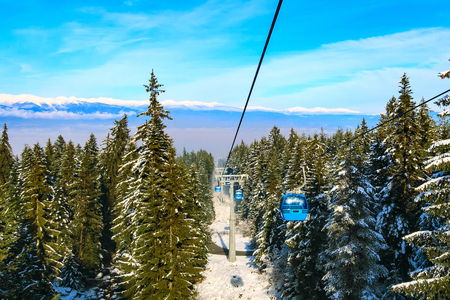 Bansko, Bulgaria winter ski resort panoramic aerial view with, cable car cabins, pine tree forest and snow mountain peaks
