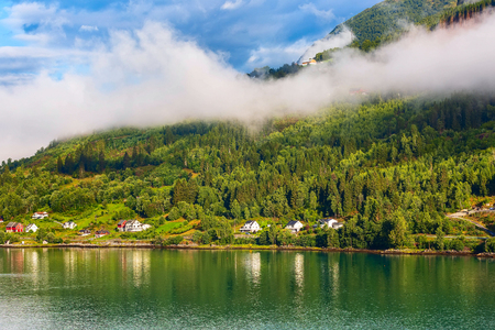 Norwegian village landscape with fjord, mountains with clouds and colorful houses, lighthouse in Olden, Norway 版權商用圖片