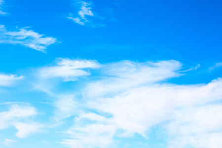 Idyllic white fluffy clouds in the blue sky lightened by sun rays
