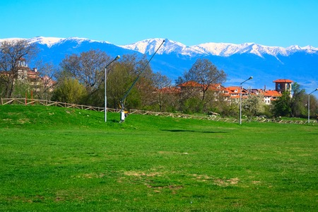 Spring landscape with green grass, houses roofs and snow mountain peaks of Pirin in Bansko, Bulgaria 版權商用圖片