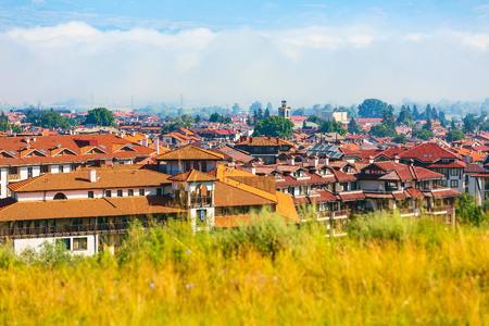 Summer aerial town panorama of bulgarian all season resort Bansko, Bulgaria with church tower and low clouds