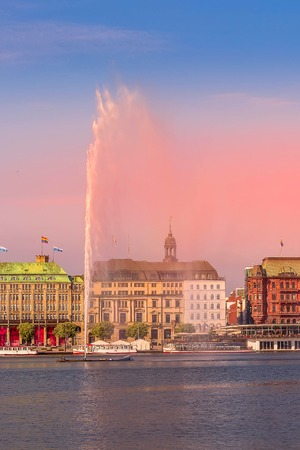 Hamburg, Germany , beautiful colorful pink sunset or sunrise view of city center with fountain and Alster lake