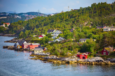Norwegian scandinavian scenic landscape with fjord water, mountains and colorful traditional houses, Norway