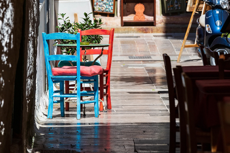 Nafplio, Greece old town view with red and blue colorful table and chairs in small street cafe in Nafplion, Peloponnese 版權商用圖片