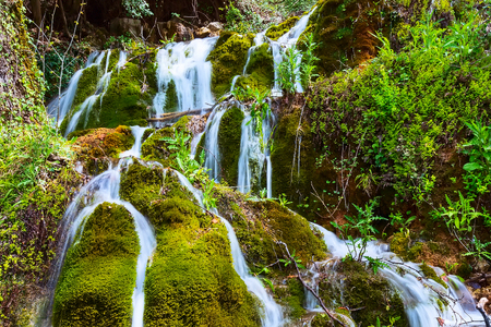 Beautiful waterfall cascade in the forest, spring nature background