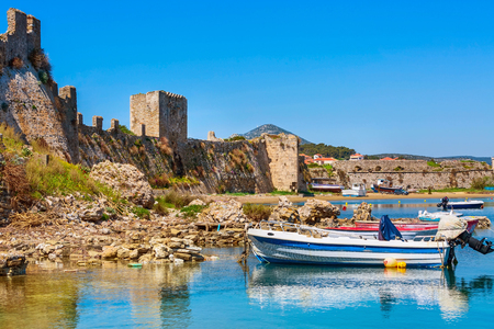 Reflection in water of castle of Methoni in Messinia, Peloponnese, Greece and fishing boats