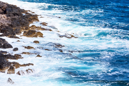 Waves hitting blue sea shore with rock stones and white foam background