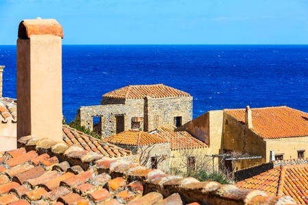 Monemvasia old red brick houses, roofs in ancient town and blue sea view, Peloponnese, Greece Stock fotó