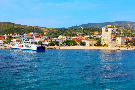 Porto di Ouranoupolis, traghetto e antica torre di Ouranoupoli , Athos, Grecia. Vista dal mare Egeo