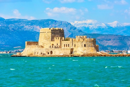 Bourtzi fortress in the sea in Nafplio or Nafplion and snow mountain peaks in Greece, Peloponnese 新聞圖片