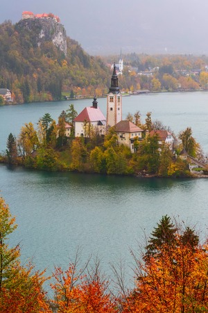 Aerial morning view of Lake Bled with Church, Slovenia and autumn colorful trees background