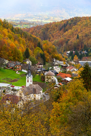 Mountain village slovenian countryside houses, church and autumn forest with colorful fall trees, Slovenia 版權商用圖片