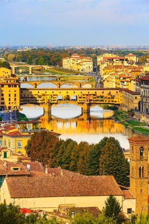 City panorama with houses and Ponte Vecchio across the river Arno, Florence, Italy