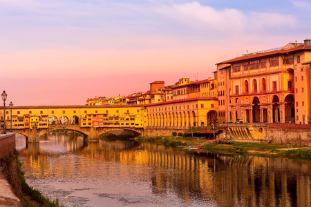 Sunset view of Vasari Corridor and Ponte Vecchio in Florence, Tuscany, Italy and reflection in the river Arno
