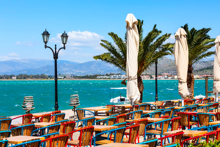 Promenade with colorful tables and chairs in street tavern restaurant, palm trees and sea in Nafplio or Nafplion, Greece, Peloponnese