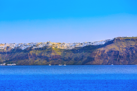 Sunrise panoramic view of Oia village in Santorini island with colorful houses and blue sea, Greece